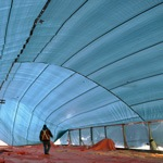 Tarp over pre-fabricated building construction site