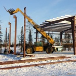 Heavy equipment working on a pre-fab steel building